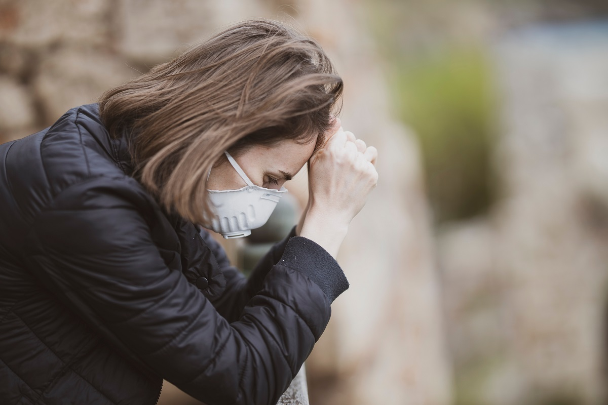 woman experiencing pandemic-induced stress while wearing mask